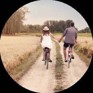 Vrouw en man hand in hand op fiets over zandpad