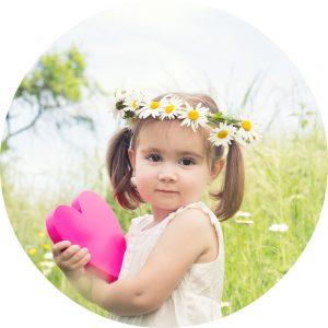 Meisje met roze hart in handen en bloemenkrans op hoofd in wei