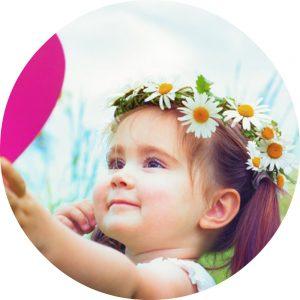 Close-up meisje met roze hart in hand en bloemenkrans op hoofd